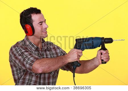 Man protecting his ears whilst drilling