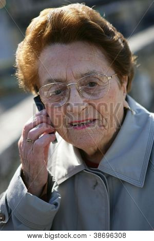 Elderly lady making call outdoors