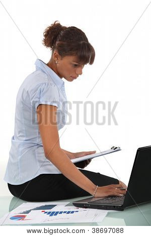 Woman sitting on her desk with a clipboard and laptop