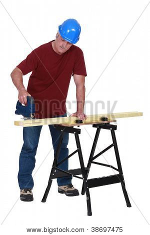 Carpenter sawing plank of wood with band-saw
