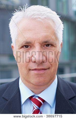 Senior business man with blank expression on his face