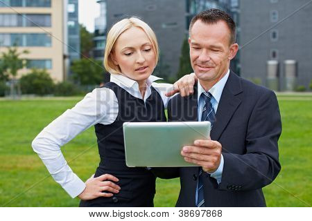Business manager and assistant working with tablet PC outside