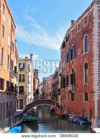 Eternal fabulous Venice. Through a narrow channel constructed an elegant bridge. Gondola approached by the walls of houses