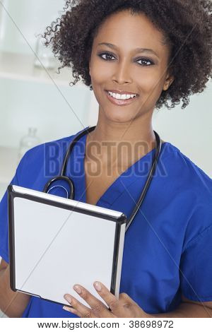 A black African American female medical doctor with stethoscope using a tablet computer in a hospital