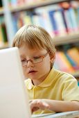 stock photo of diligent  - Portrait of serious schoolkid working with laptop in the library - JPG