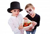 stock photo of antichrist  - Photo of two eerie boys with sack of Halloween treats looking at camera - JPG