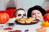 pic of antichrist  - Photo of two eerie boys looking at cookies on Halloween table - JPG