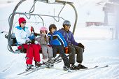 stock photo of lifting-off  - Family Getting Off chair Lift On Ski Holiday In Mountains - JPG