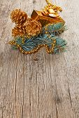 foto of shaky  - Christmas golden decorations on pine branch on wooden background - JPG