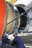 airplane mechanics calibrating large jet engine, standard practice