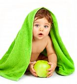 Photo of cute little boy eating big fresh apple, adorable child covered green towel isolated on whit