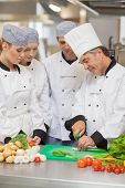 picture of scallion  - Chef teaching cutting vegetables to three trainees in the kitchen - JPG