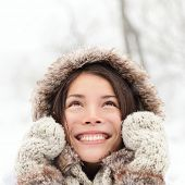 Winter woman looking up happy and smiling outdoors in snow on cold winter day. Asian girl model in h