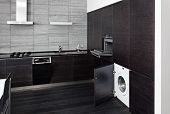 Part of black hardwood kitchen with build-in domestic technique poster