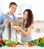 Young Man Cooking. Happy Couple on a Kitchen at Home Eating Fresh Vegetable Salad.Diet.Dieting. Loos