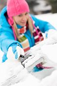 stock photo of ice-scraper  - Woman brushing snow from car windscreen winter work scraper wiping - JPG