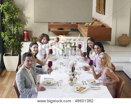 Retrato de grupo de amigos multiétnicas tostado copas de vino en la cena