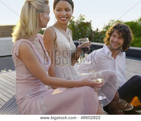 Three young friends drinking and socialising on porch