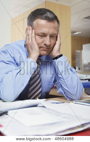 Pensive middle aged businessman sitting at office desk