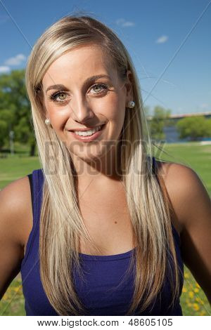 Portrait Of A Young Blond Woman Smiling Outside