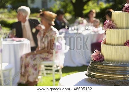 Closeup of wedding cake with guests sitting at tables in background