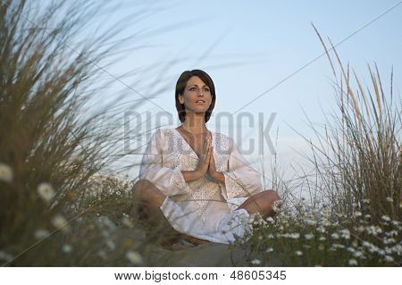 Low angle view of a young woman meditating on sand dune against sky
