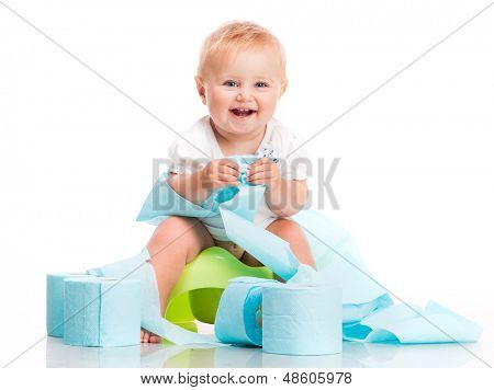 little baby sitting on a pot and keeps the toilet paper. studio photo on white