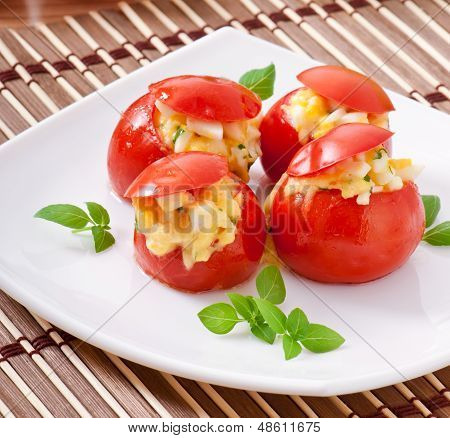 Tomatoes stuffed with cheese, egg with fresh herbs basil