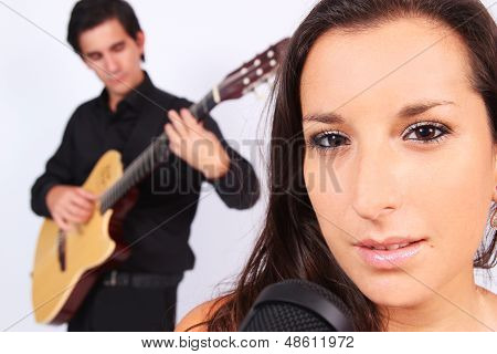 A Female Singer And A Male Guitarrist In Action