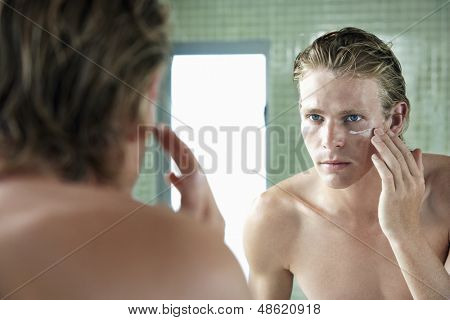 Handsome young man applying moisturiser cream in front of mirror