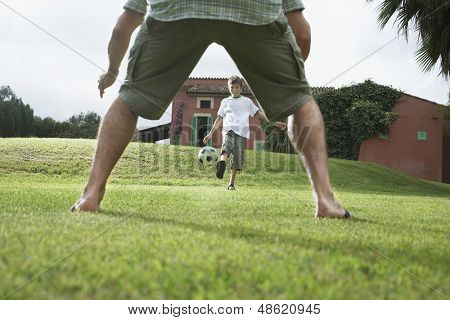 Lowsection of father with son playing football in backyard