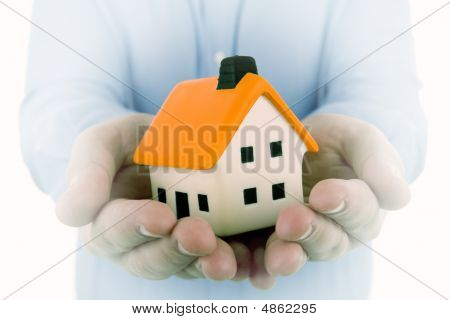 Man Holding A Small House In His Hands With Dream Effect To Enphasize The House