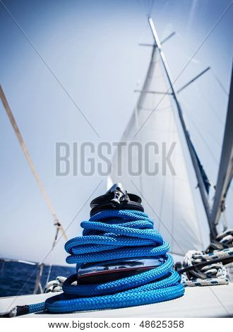 Closeup on yacht cord crank, rope holder on white sail background, yachting sport, sailboat detail, luxury water transport, summer vacation concept