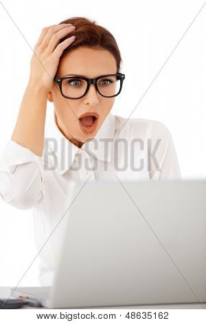 Beautiful businesswoman wearing glasses looking at her laptop in horror with her hand raised to her head and mouth open