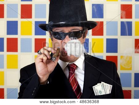 Middle aged repulsive businessman is smoking cigar and showing off his money.