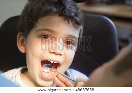 Dentist is checking and treating little boy's teeth.