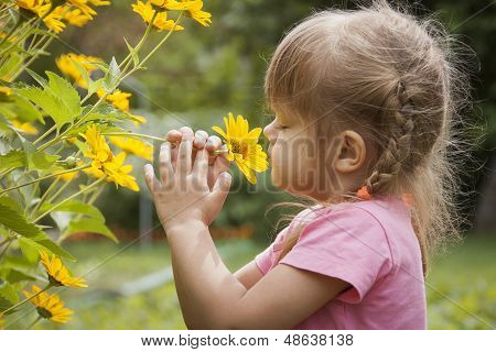 Three-year girl sniffing yellow flower