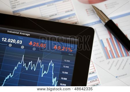 Analysing stock market with digital tablet.