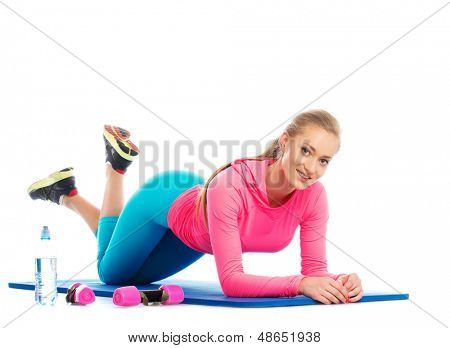 Beautiful girl doing fitness exercise on a floor mat