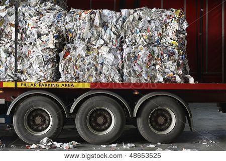 Stacks of recycled papers on lorry in recycling plant