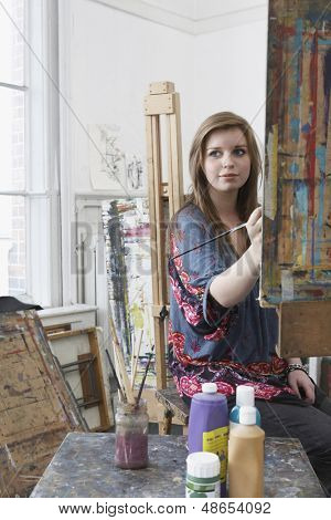 Young female artist painting at easel in art studio