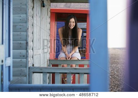 Portrait of happy young woman sitting on balustrade of beach house