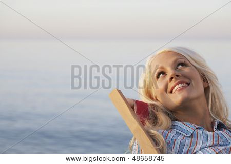 Happy young woman looking up while relaxing on lounge chair at beach