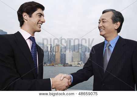 Two businessmen shaking hands with cityscape in background