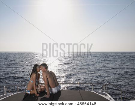 Romantic couple rubbing noses while sitting on yacht's edge by sea