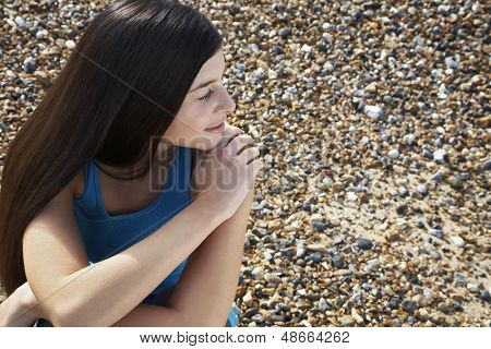 Thoughtful young woman looking away while sitting at beach