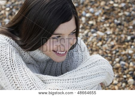 Closeup of thoughtful young woman looking away while sitting at beach