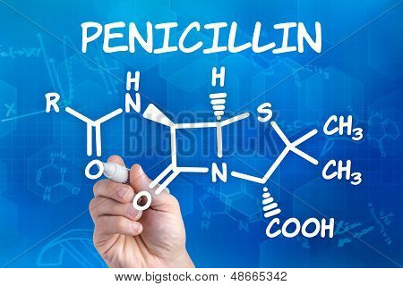 hand with pen drawing the chemical formula of Penicillin