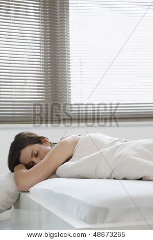 Side view of young woman sleeping in bed at home