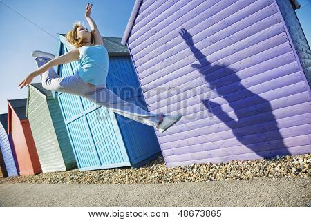 Full length of young woman jumping in front of beach huts during summer